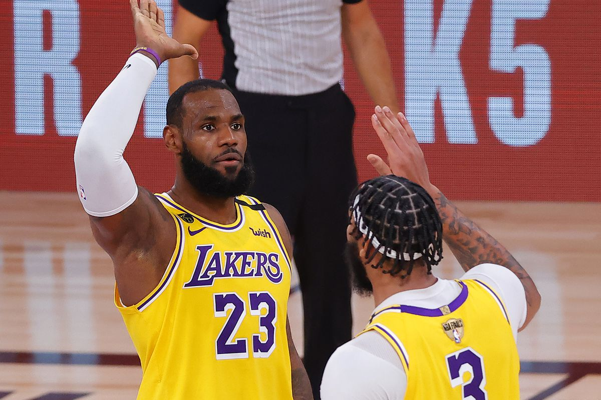 Anthony Davis of the Los Angeles Lakers reacts to a basket with LeBron James of the Los Angeles Lakers during the third quarter against the Miami Heat in Game One of the 2020 NBA Finals at AdventHealth Arena at the ESPN Wide World Of Sports Complex on September 30, 2020 in Lake Buena Vista, Florida.