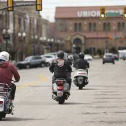 Two Bit Scooter Club riders motor down 25th Street in Ogden during a safe ride amid the coronavirus pandemic on Sunday, April 19, 2020.