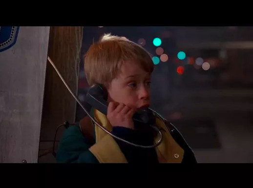 A boy in outdoor winter clothing stands at a payphone with the phone to his ear. It is night and in the background are city lights.