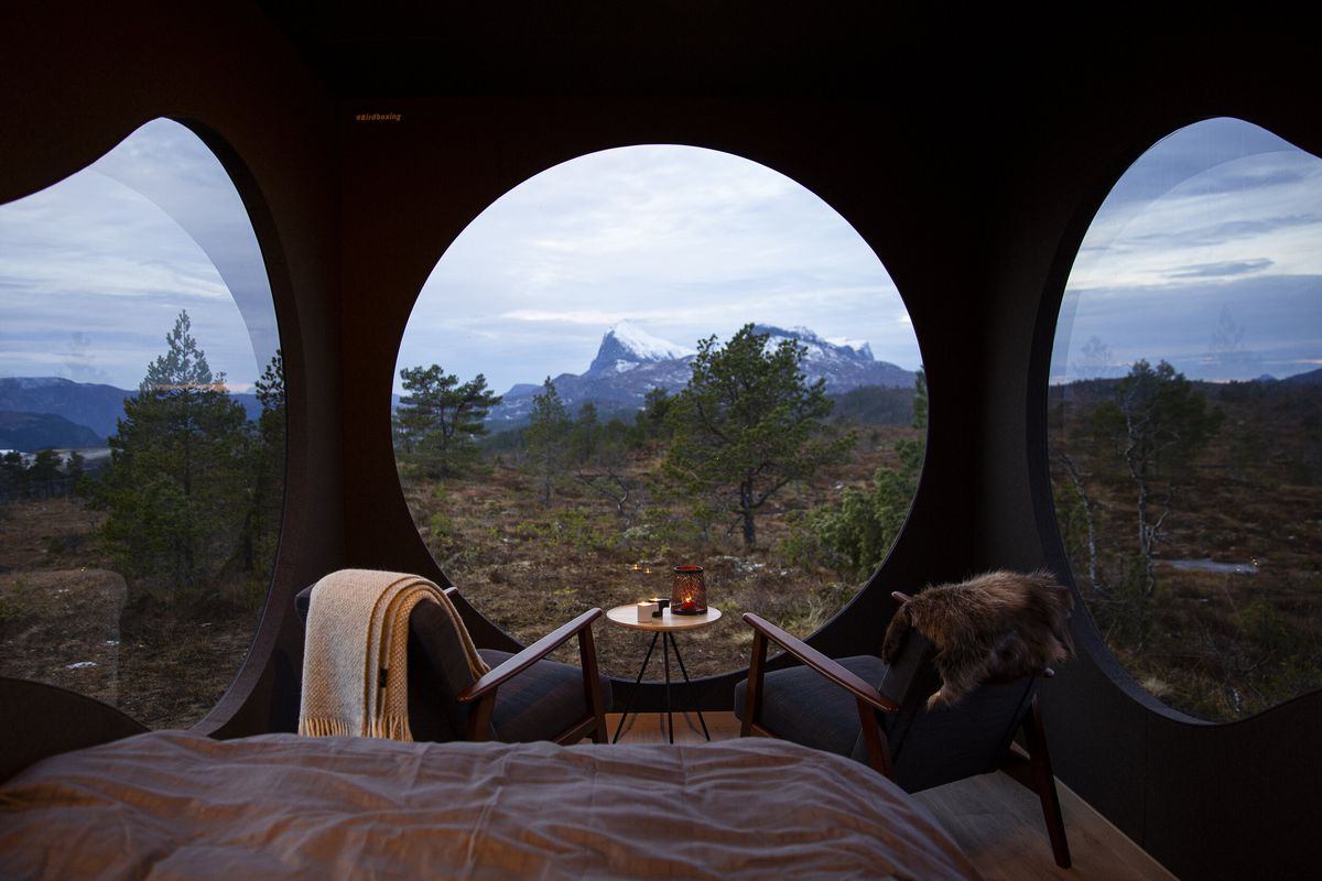 Round windows looking out onto mountains.