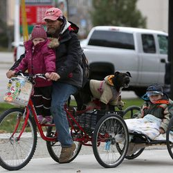 Lakota Beal, Fred Rivers, dogs Diamond and Soks, and Todd Jr. Dickerman leave the 10th annual Community Coat Exchange at Pioneer Park in Salt Lake City on Friday, Nov. 28, 2014.