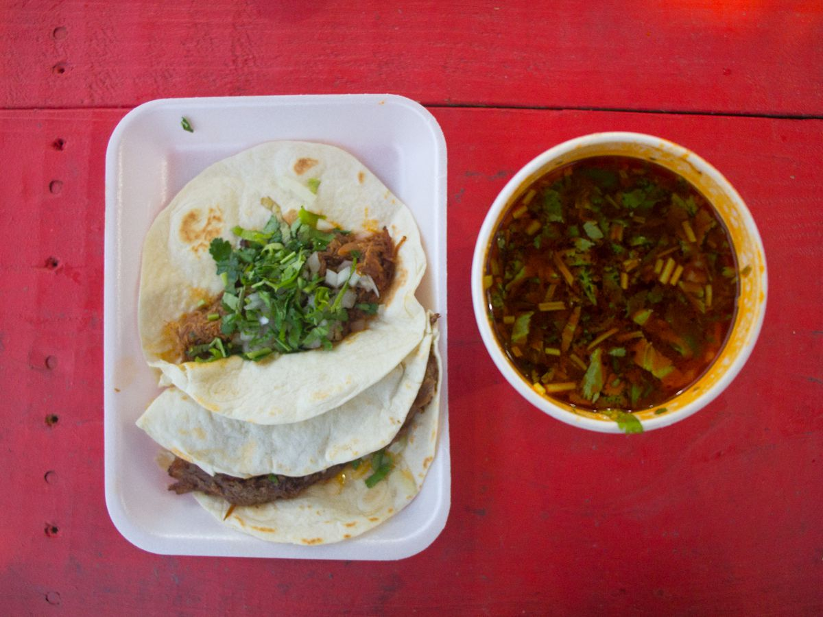 A styrofoam plate of two tacos with meat, cilantro, and diced onions on the left next to a styrofoam cup of consomme on a red table