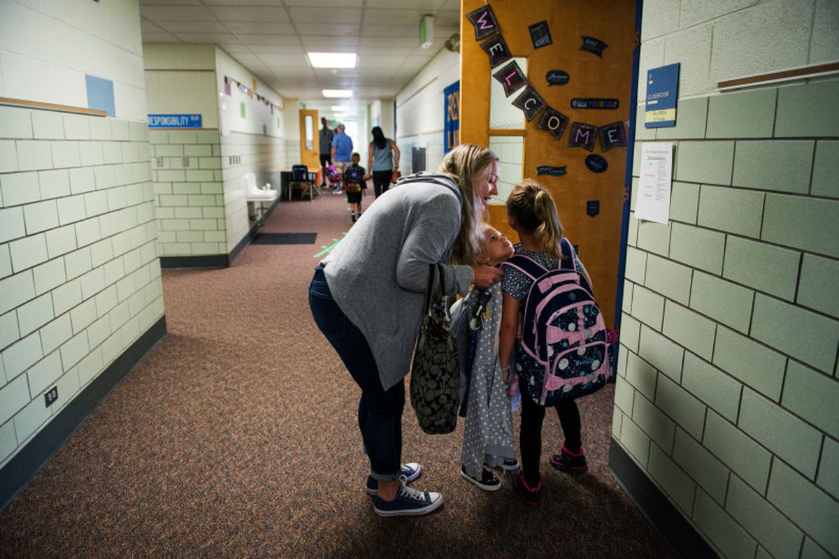 Mae Simpson leans down to talk to her daughter Stella before dropping her off for her first day of third grade in Arvada.