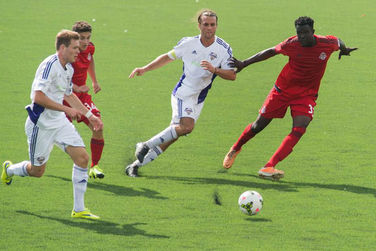Matt Fondy and Magnus Rasmussen chase a ball agasint Toronto FC II