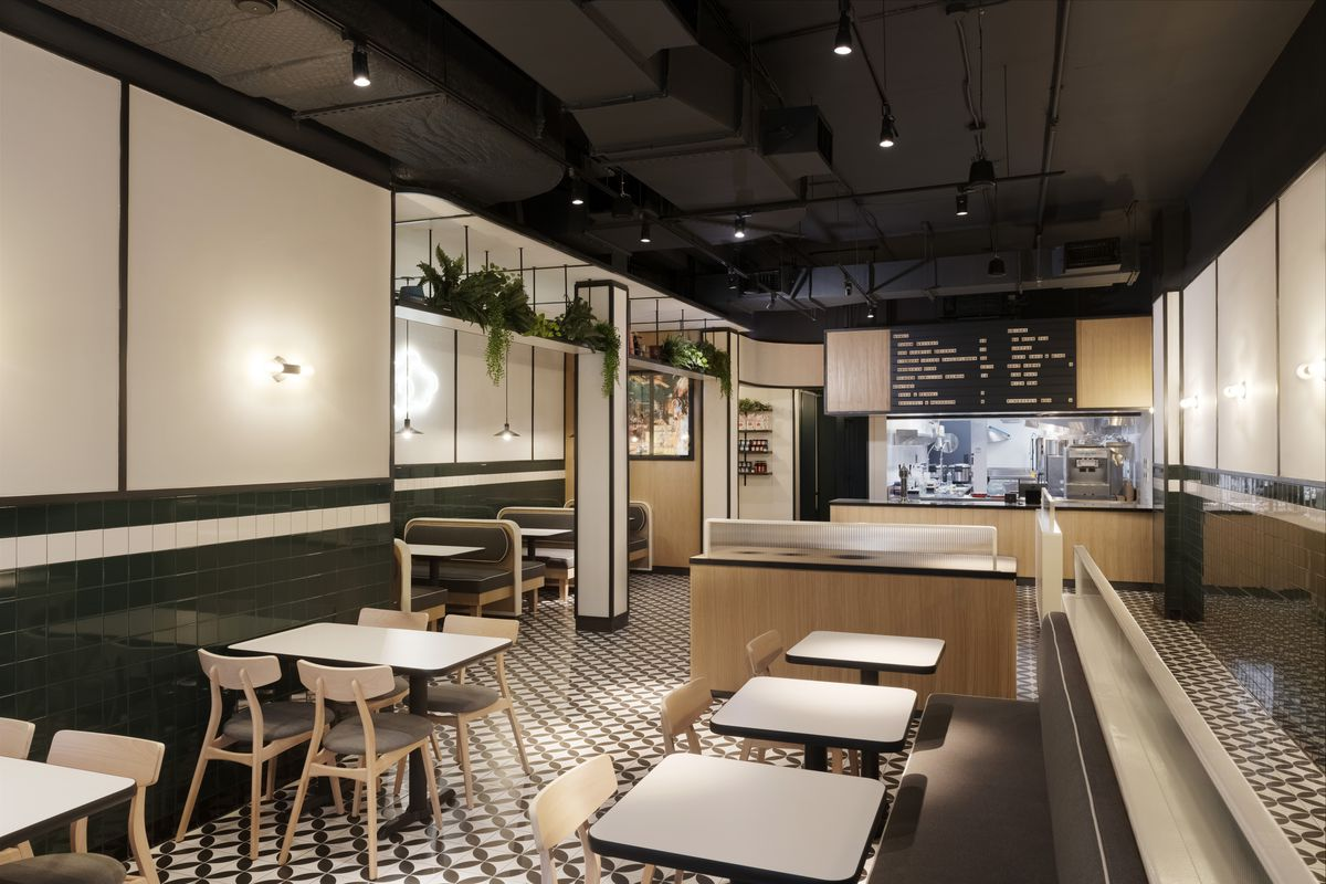Sets of white tables and chairs sit in an empty cafeteria-style dining room. At the back of the room, there's a counter where customers can order fast-casual-style bowls.