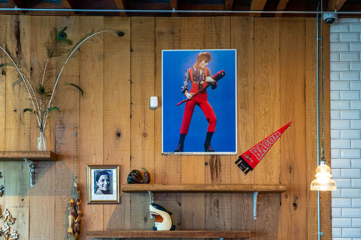 A poster of David Bowie from the Ziggy Stardust area prominently displayed on a wood-paneled wall, alongside a small shark statue and peacock feathers