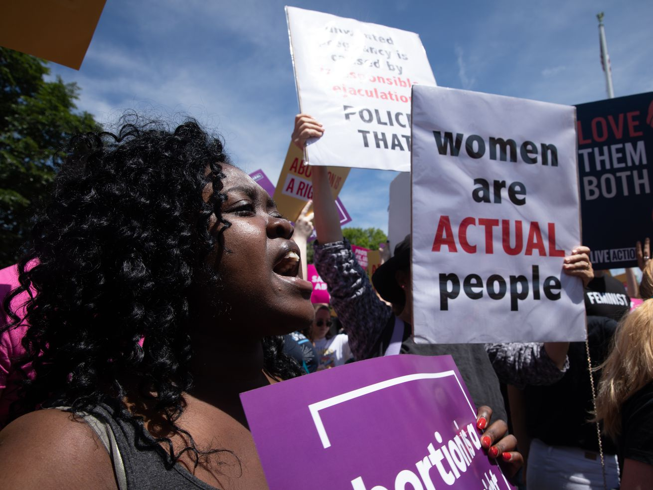 """Activists on both sides of the abortion issue demonstrate outside the U.S. Supreme Court on May 21, 2019. One holds a sign saying, """"Women are actual people."""""""
