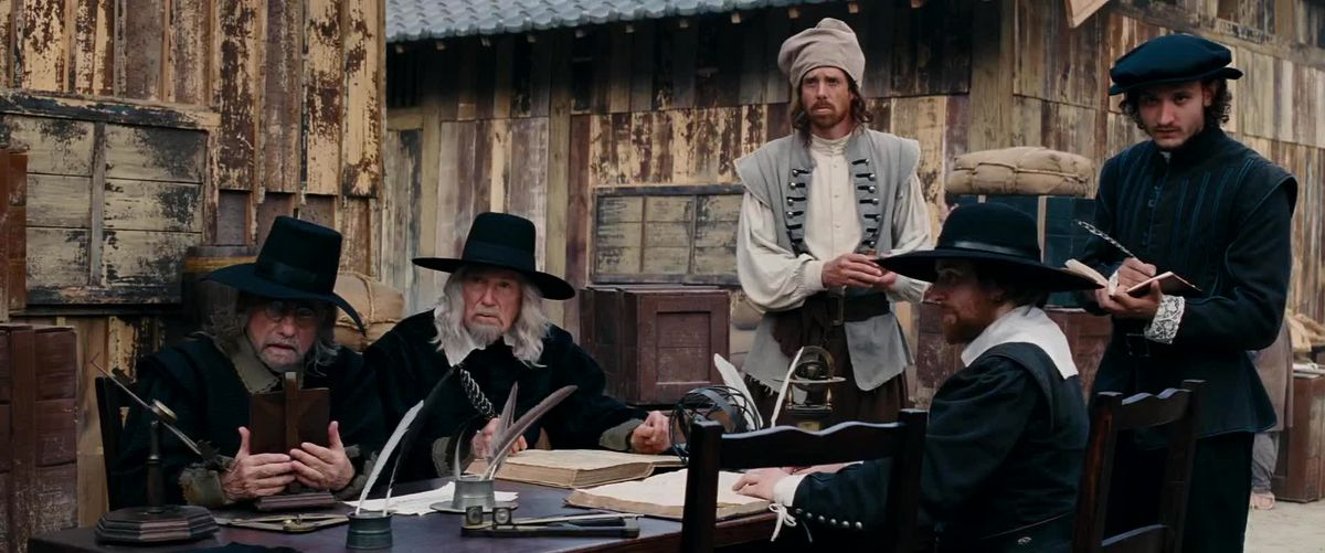 Martin Scorsese dressed as a Puritan sitting at an outdoor table with other black-clad men in 2016's Silence