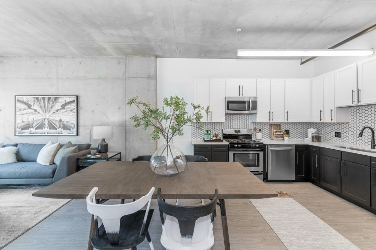 A view of the open layout apartment with a concrete ceiling, wooden table, white cabinets in the kitchen, and a blue sofa.