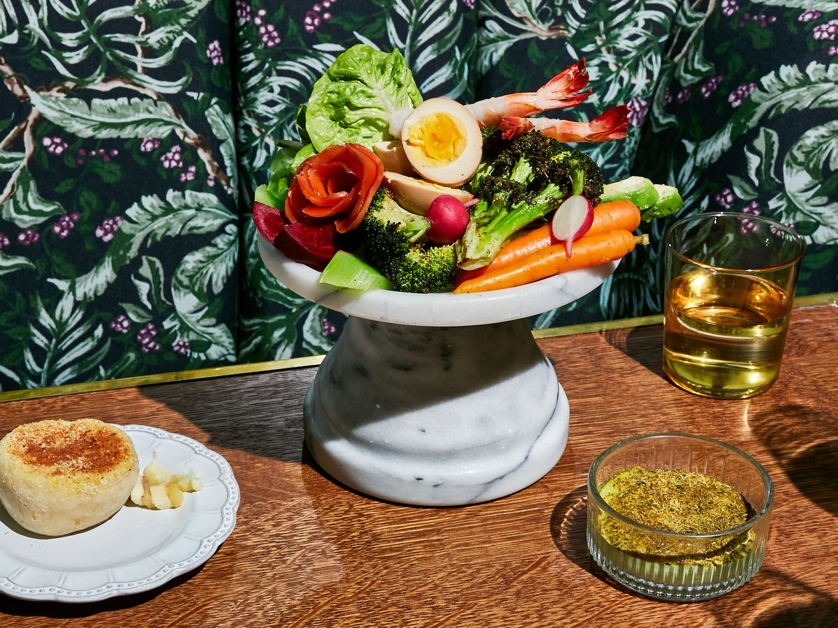 The grand aioli features fresh vegetables including some cut into rosettes with poach shrimp and boiled eggs on a tower made from marble. A white plate with a single English muffin sits off to the side along with a crystal dish of dip and a clear stemless glass of white wine.