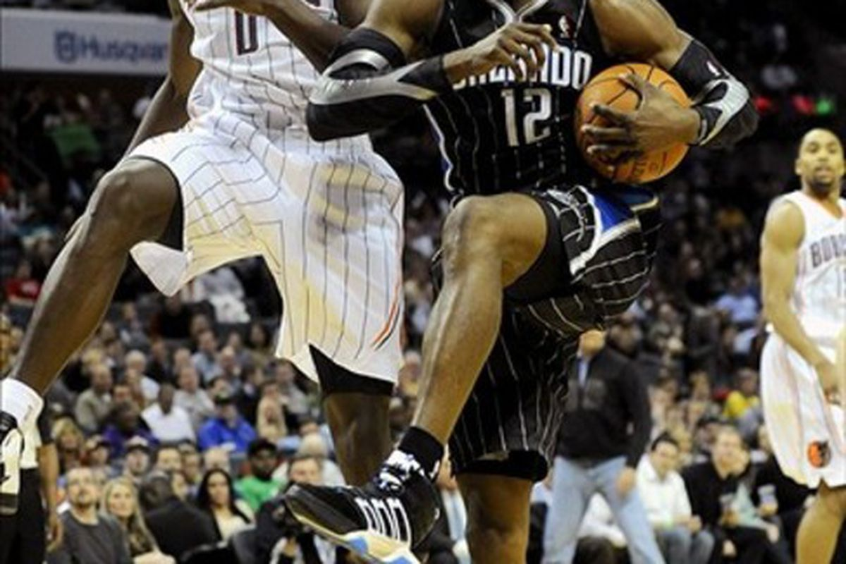 March 6, 2012; Charlotte, NC, USA; Orlando Magic center Dwight Howard (12) gets a rebound against Charlotte Bobcats center Bismack Biyombo (0) during the game at Time Warner Cable Arena. Bobcats win 100-84. Mandatory Credit: Sam Sharpe-US PRESSWIRE