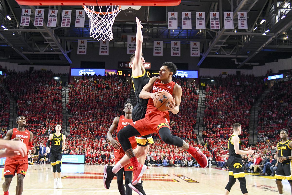 Maryland Terrapins guard Anthony Cowan Jr. makes a pass under the basket in the second half against Iowa Hawkeyes guard Joe Wieskamp on January 30, 2020, at Xfinity Center in College Park, MD.