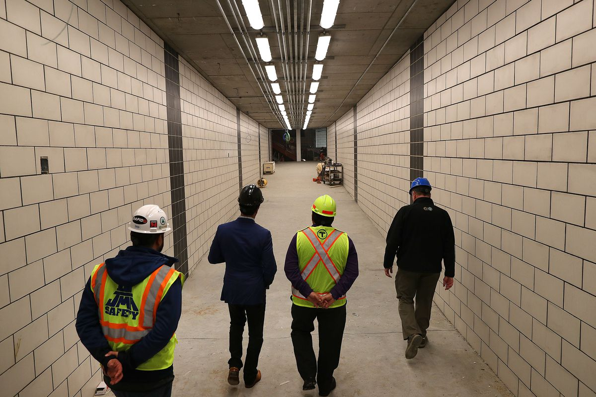 Four people walk down a tunnel that has white tiles and a painted black ceiling with bright lights. Two of the people are wearing colorful safety vests. All of the people are wearing construction hard hats.