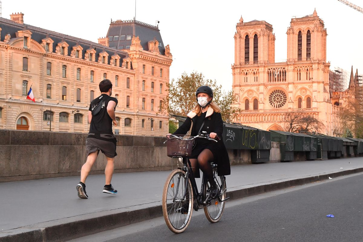 A jogger runs and a woman wearing a mask rides her bicycle next to Notre Dame Cathedral in Paris, France.