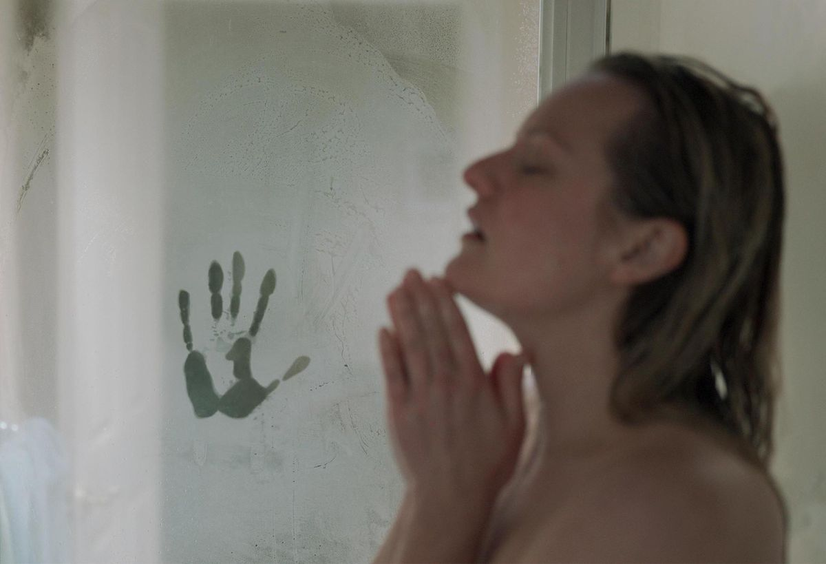 Elisabeth Moss in the shower with a mysterious handprint on the fogged-up door in The Invisible Man