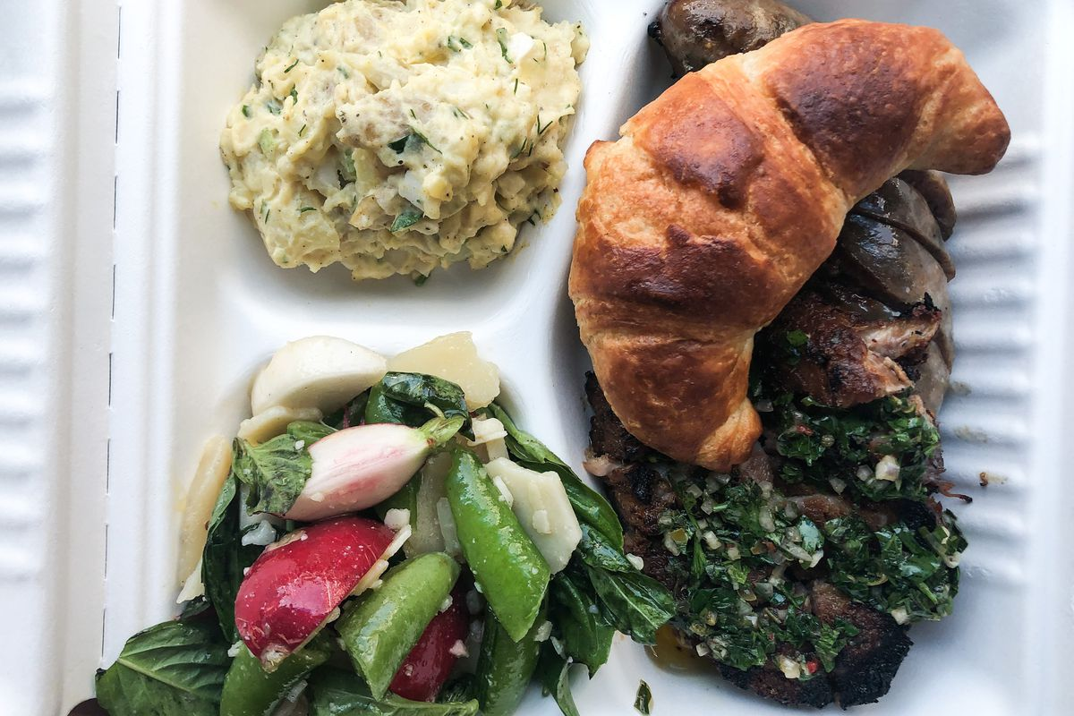 A takeout container with three compartments is full of a basil-heavy radish salad, white potato salad, and a pile of chimichurri-covered pork shoulder at Lazy Susan. The sausage is covered with a crescent roll.