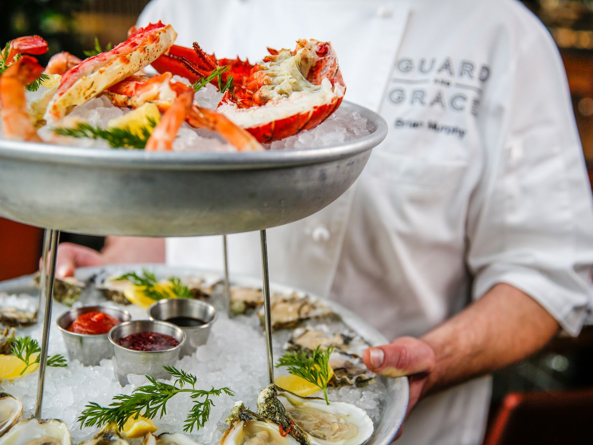 a two-level seafood tower with crab on top and oysters on ice on the botttom. the tower is being carried by a person in a white apron