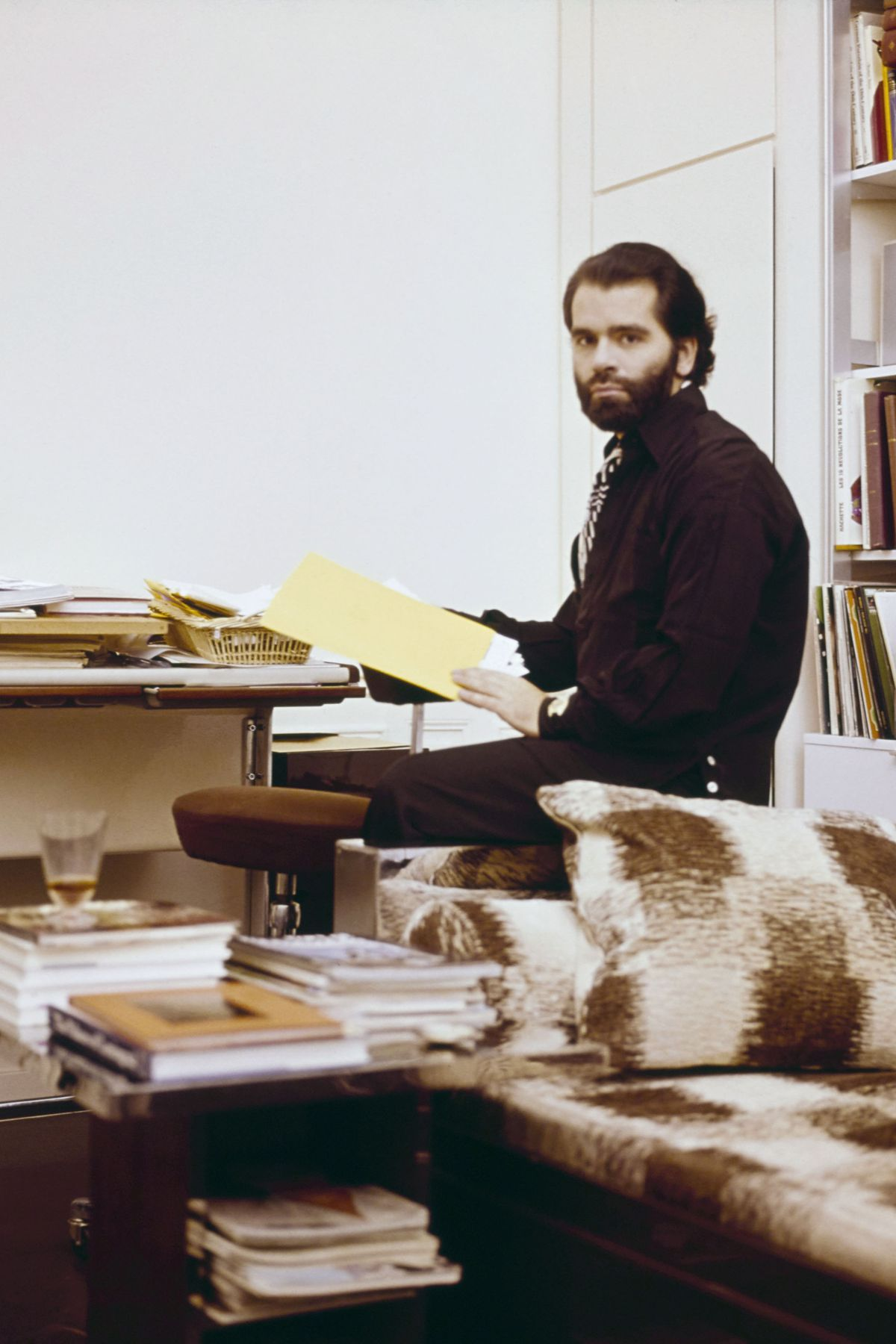 A young man with a beard and slicked back dark hair sits at a desk with a large manila folder in his hands. In the foreground there is a corner of a couch with a checkered ikat pattern and a glass coffee table stacked with large books.