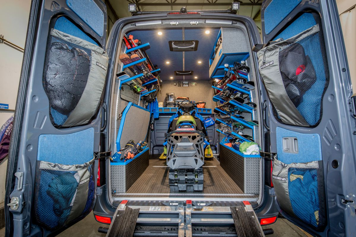A rear view of a blue and gray camper van with doors open, a ramp, and a snowmobile in the center. On the side of the interior of the van are racks for skis and flip-down beds.