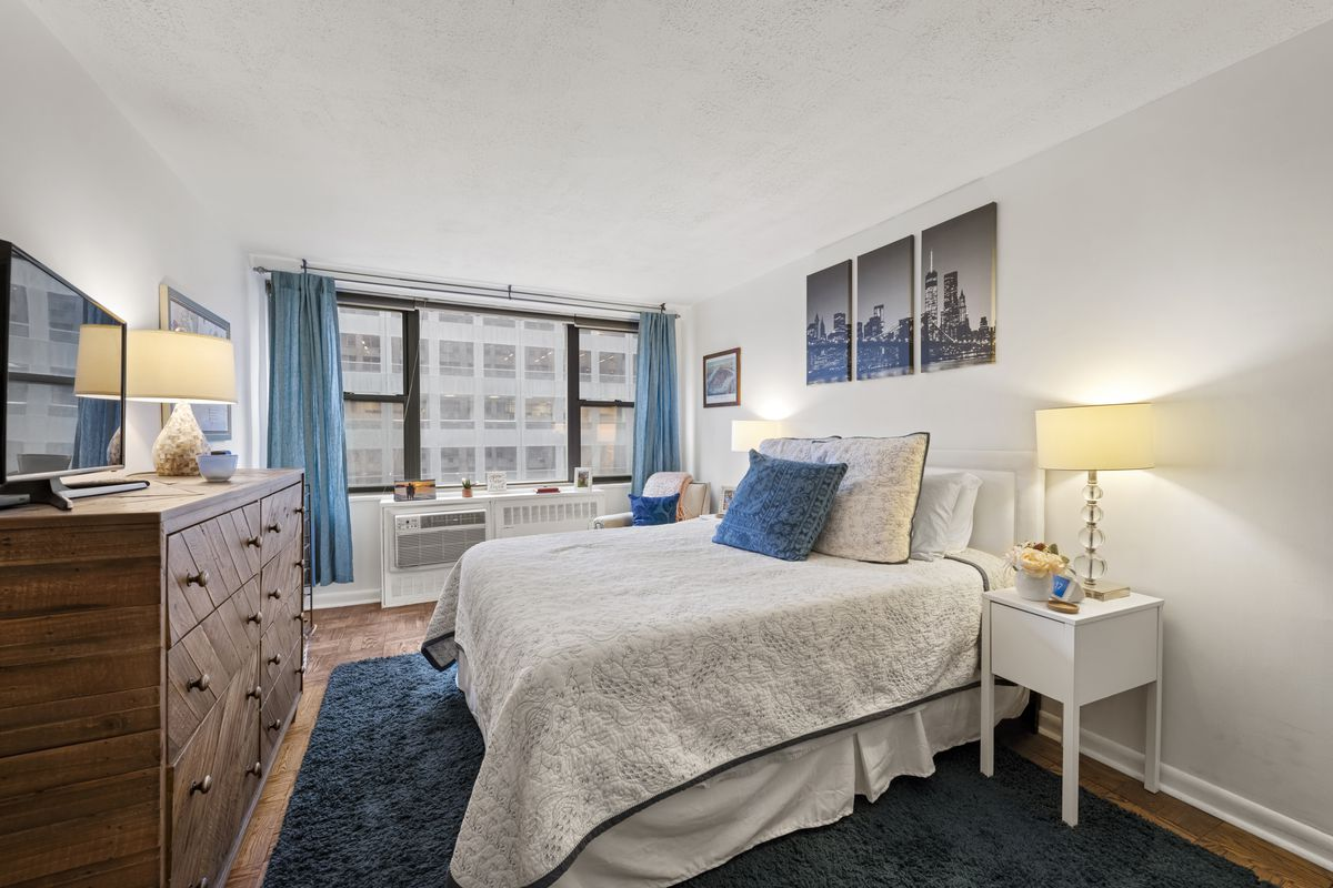 A bedroom with a medium-sized bed, hardwood floors, a large window, and wooden cabinets.