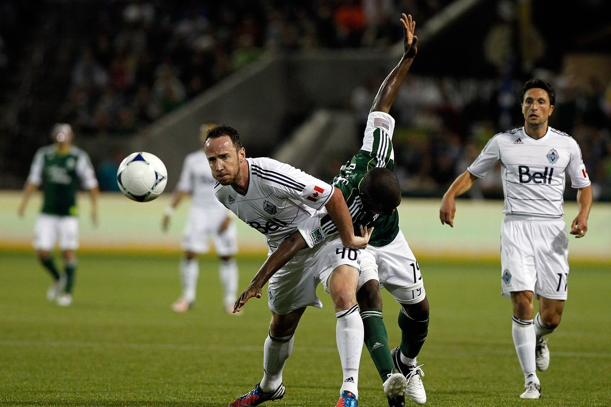PORTLAND, OR - AUGUST 25: Bright Dike #19 of the Portland Timbers battles Andy O'Brien #40 of the Vancouver Whitecaps on August 25, 2012 at Jeld-Wen Field in Portland, Oregon. (Photo by Jonathan Ferrey/Getty Images)