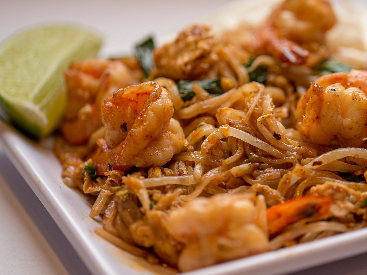 A bowl of pad thai with large grilled shrimp and a lime wedge on a white background