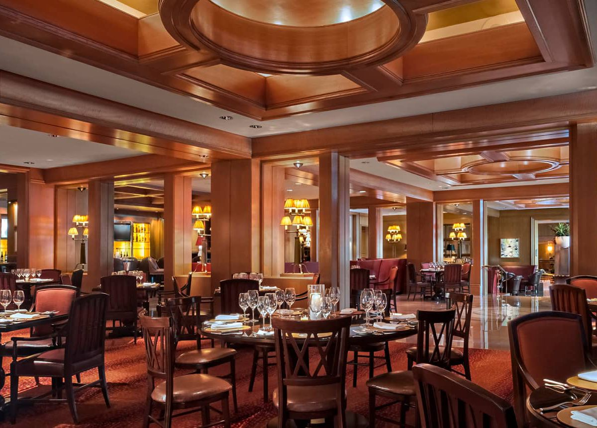 A capacious hotel lounge with several tables and soft lighting.