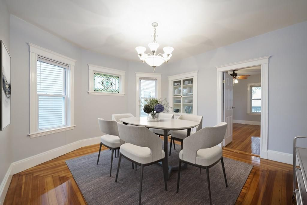 A dining room with a table and chairs, and a bay window and an opening to another room.