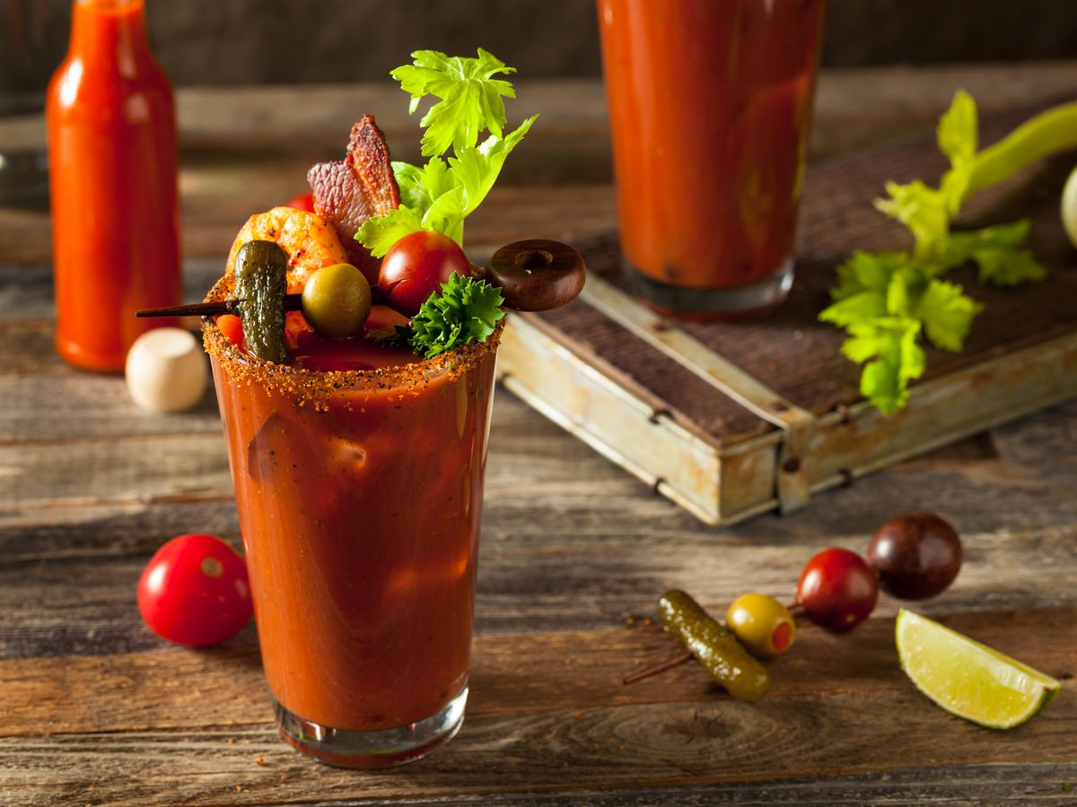 A glass of bloody mary with celery and other garnishes on a wooden table, with ingredients scattered around.
