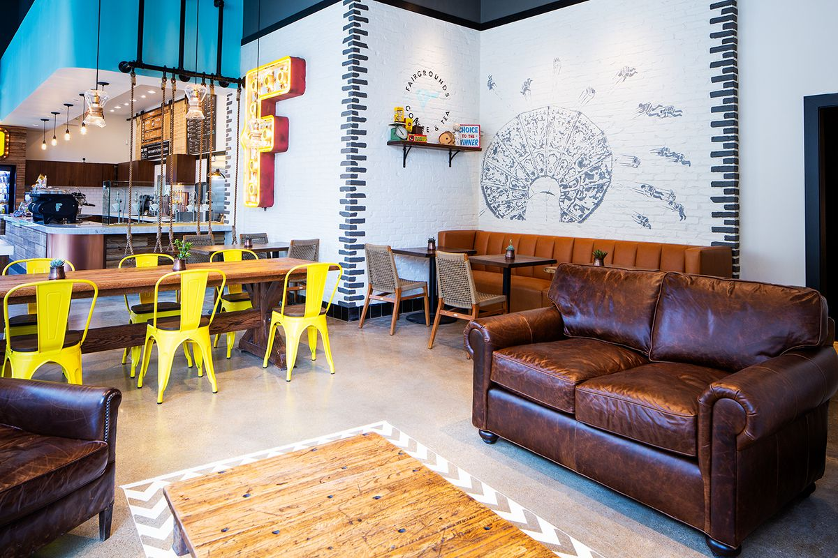 The interior of Fairgrounds Coffee in Dallas, with a cozy leather couch and bright yellow chairs
