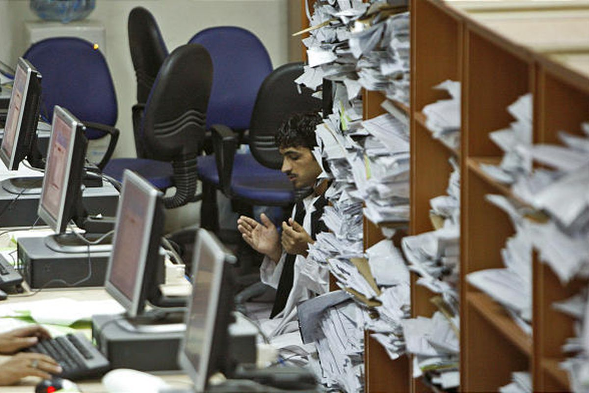 An election worker is partially seen through sheaths of documents and computer screens offering his prayers during a break while tallying results at the Independent Election Commission in Kabul, Afghanistan, Wednesday. Final, certified results won't be ma