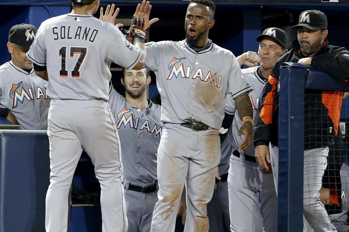 Miami Marlins' Donovan Solano, left, gets a high-five from Jose Reyes after hitting a two-run home run to score Greg Dobbs during the seventh inning of a baseball game against the Atlanta Braves on Tuesday, Sept. 25, 2012, in Atlanta.