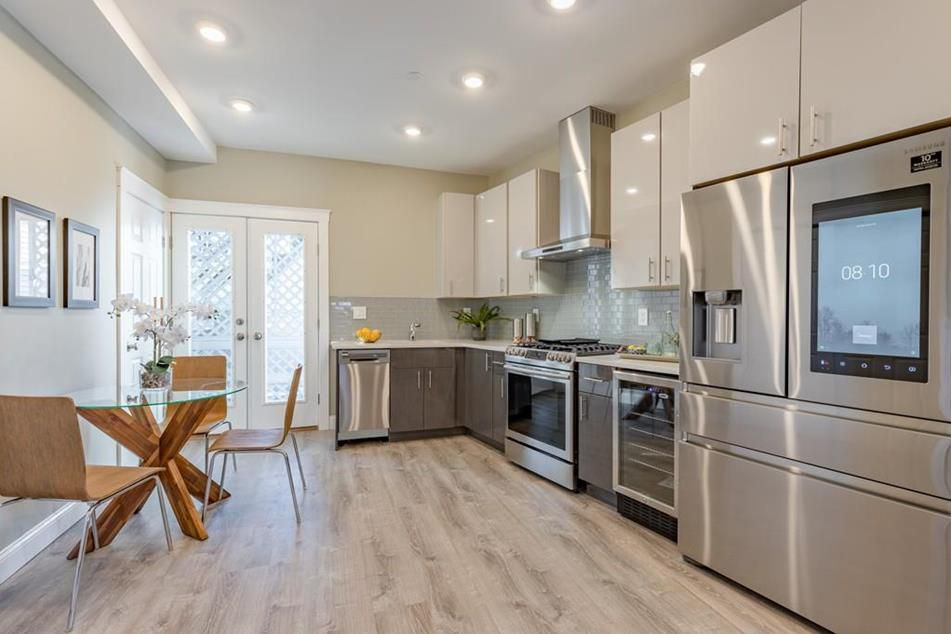 A long, modern kitchen with counters meeting at a right angle.