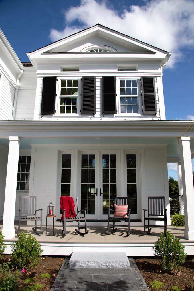 Side porch of the TOH 2019 Idea House at New Canaan, with two rocking chairs and french doors