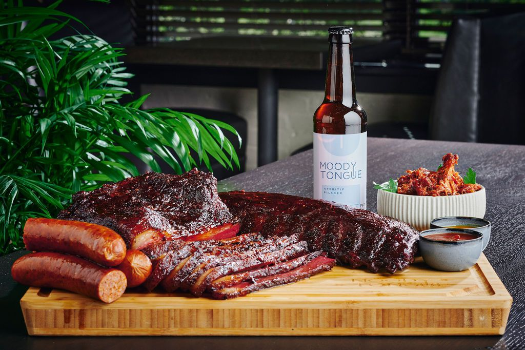 A wood cutting board with smoked meats and a bottled of beer.