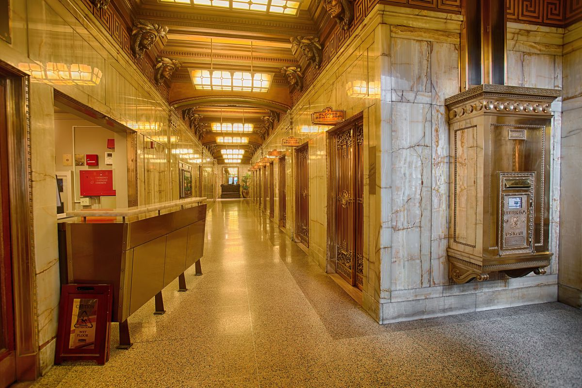 A marble-lined hallway with gold-colored vintage elevator banks along the right wall.
