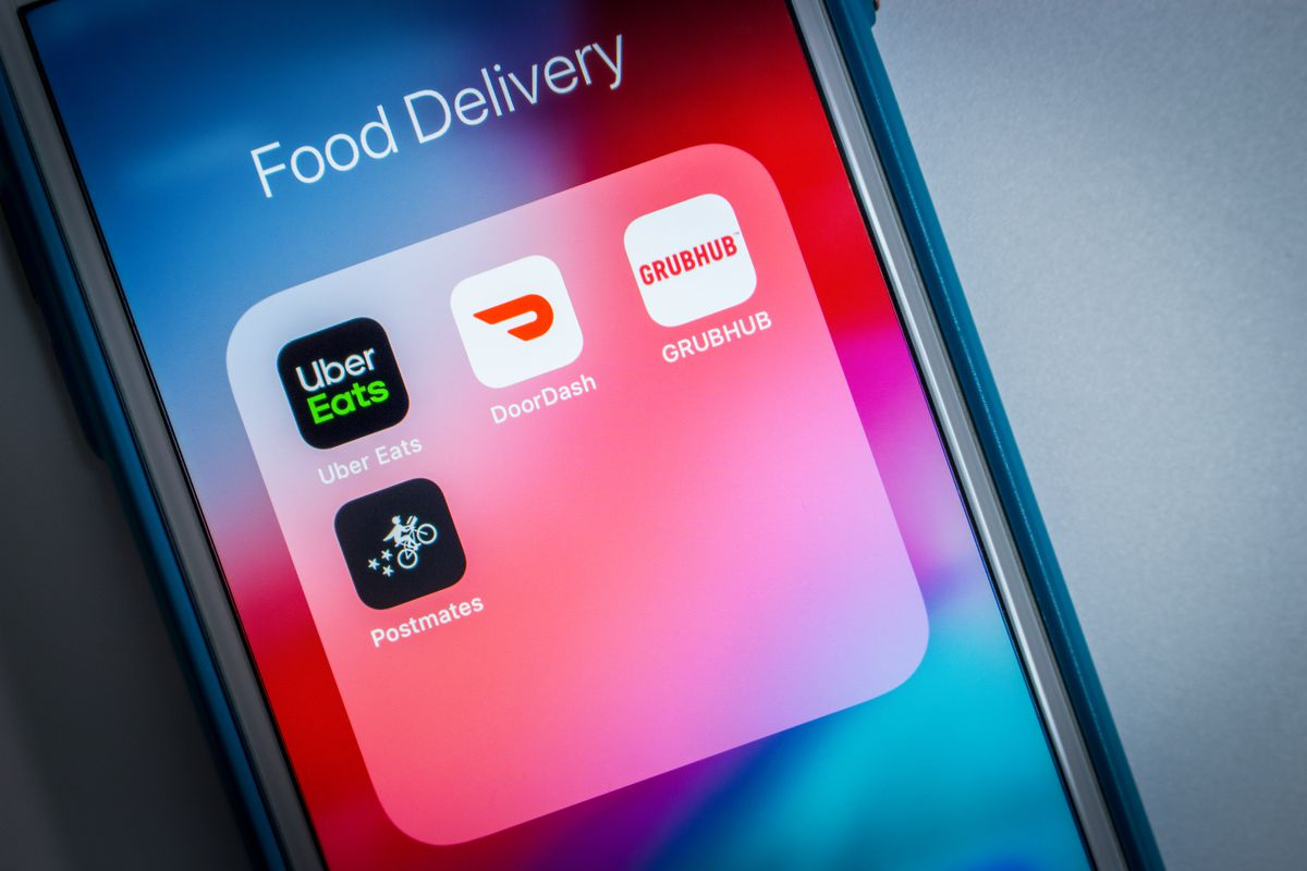 An iPhone displays a number of food delivery app icons, such as Doordash, Grubhub, and Uber Eats.