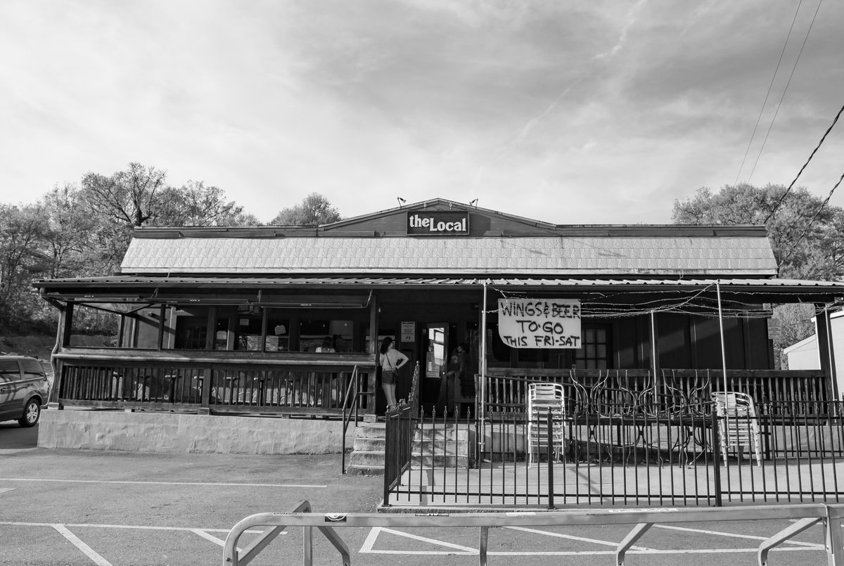The Local in March 2020 pivots to-go. A handmade sign hangs on the patio and reads wings and beer to-go this friday and saturday on a table cloth. A woman in shorts and a tee shirt stands waiting for her order