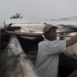 A man works to repair the roof of his tent in a camp for people displaced by the 2010 earthquake as Tropical Storm Isaac affects Port-au-Prince, Haiti, Saturday, Aug. 25, 2012. Tropical Storm Isaac swept across Haiti's southern peninsula early Saturday, dousing a capital city prone to flooding and adding to the misery of a poor nation still trying to recover from the 2010 earthquake.