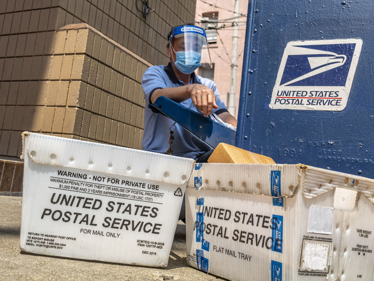 A postal worker empties a blue collection box.