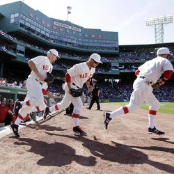 Boston Red Sox players take the field for a baseball game against the New York Yankees in throw-back uniforms of 1912 at Fenway Park in Boston, Friday, April 20, 2012. The Red Sox are celebrating  the100th anniversary of the first regular-season game at Fenway Park.