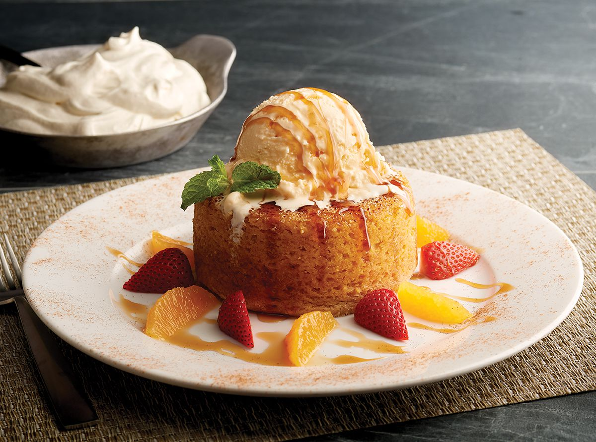 A golden round pumpkin butter cake with whipped cream and strawberries.