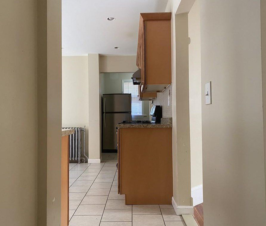 The view toward a kitchen and its counter from a hallway.