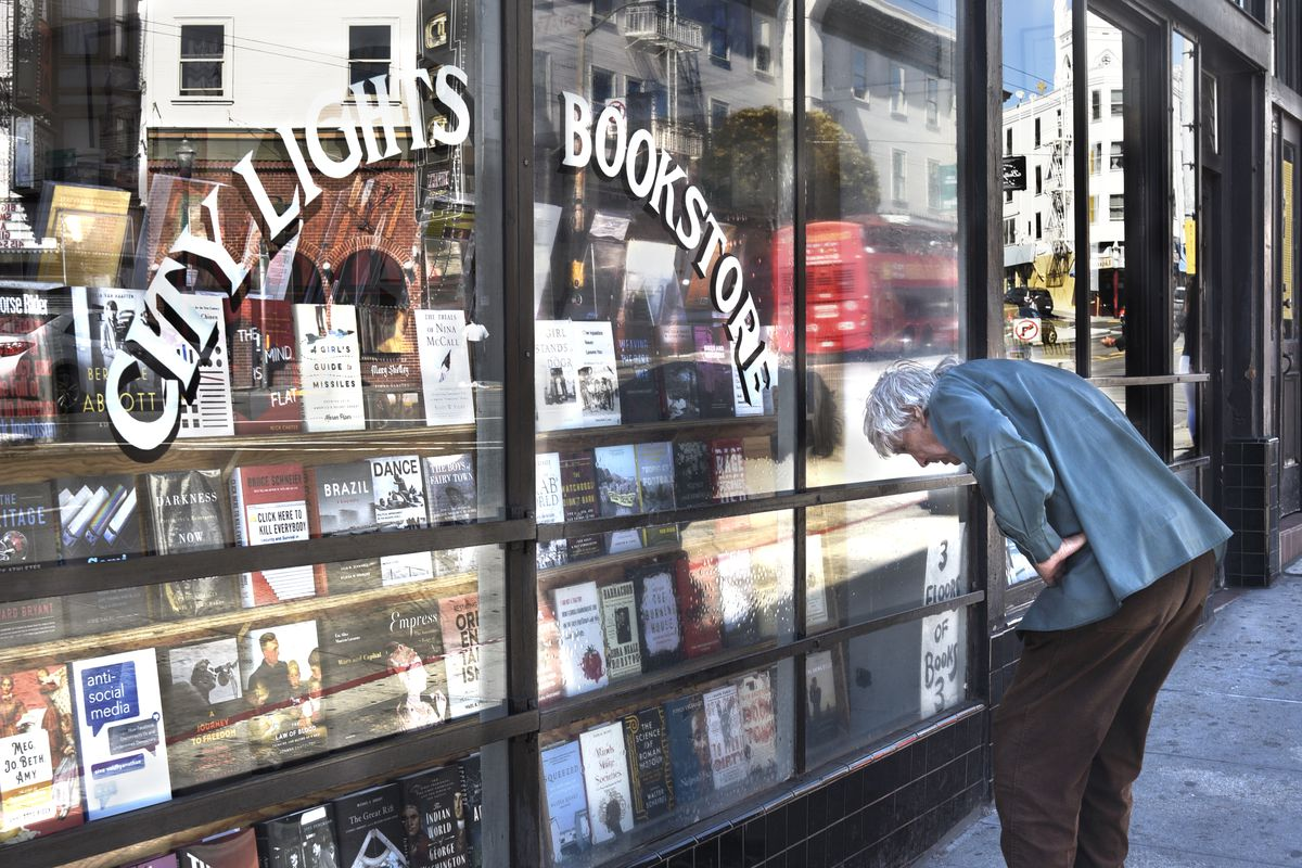 bc2b2838847 A man peruses a window display at City Lights Bookstore in San Francisco