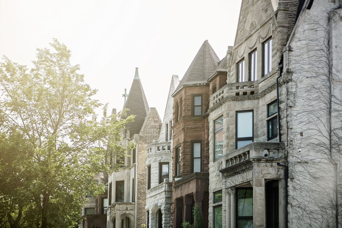 A row of greystone homes with a tree-lined parkway.