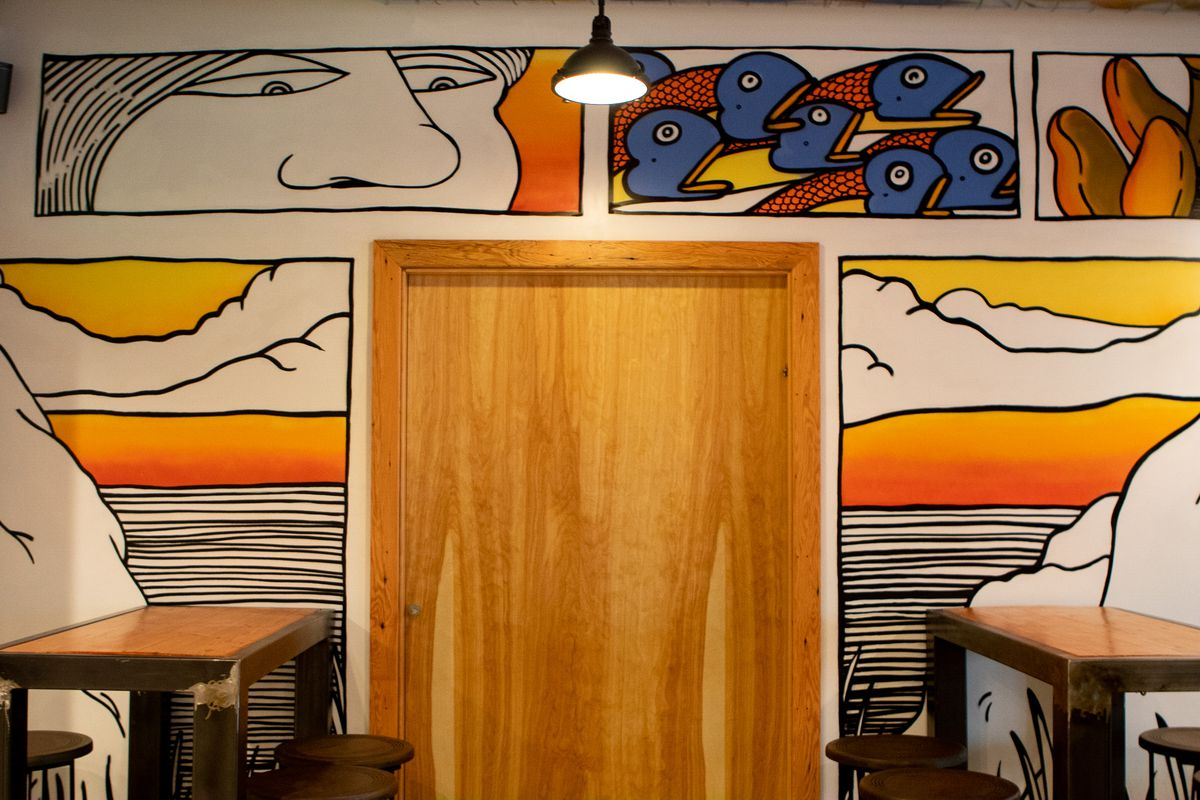 A look at a wooden door, surrounded by artwork of a woman's face, fish, and clouds.