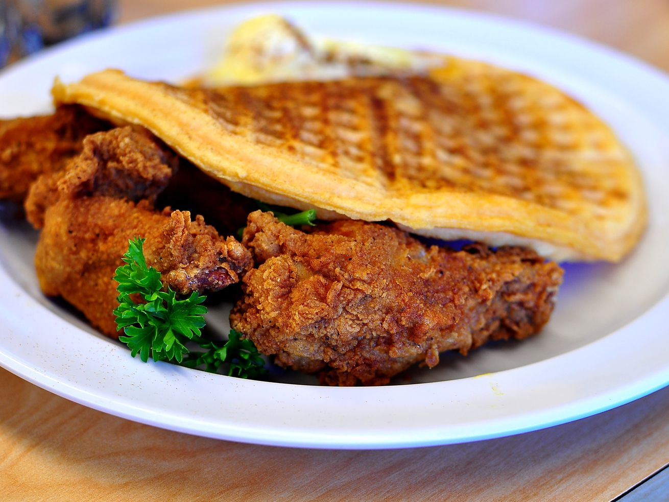 A plate of fried chicken tucked underneath a waffle from the Serving Spoon in Inglewood