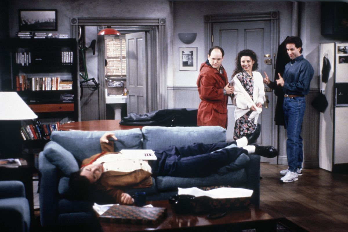 """""""Seinfeld"""" characters George, Elaine, and Jerry stand in Jerry's apartment and look at Kramer passed out on the couch."""
