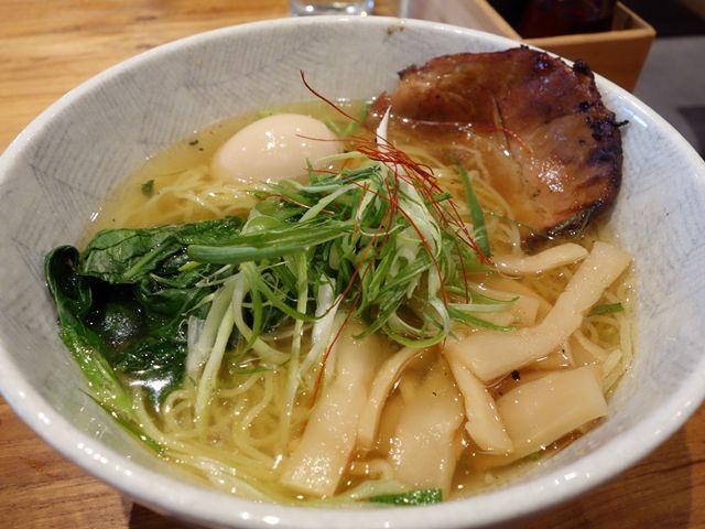 A white bowl of yuzu-shio ramen with greens and pork.