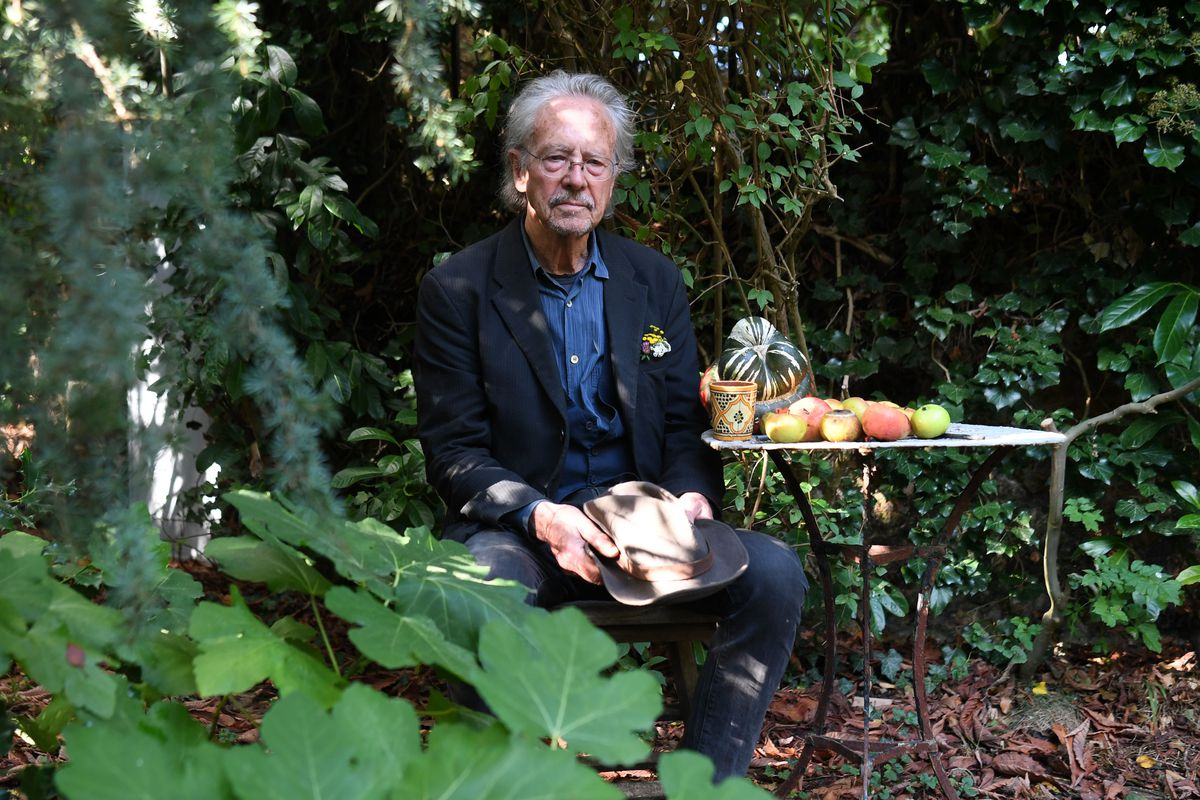Nobel Prize winner Peter Handke sitting in a shaded garden beside a table.